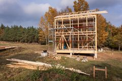 Metal scaffolding around the unfinished house. Construction of ecological house. Wooden frame of house under construction. Royalty Free Stock Photos