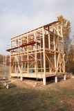 Metal scaffolding around the unfinished house. Construction of ecological house. Wooden frame of house under construction. Stock Photography