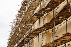 Metal scaffolding with wooden decking built around a historic building for restoration work and renovation of the facade. Construc. Metal scaffolding with wooden Stock Photography