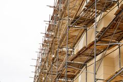 Metal scaffolding with wooden decking built around a historic building for restoration work and renovation of the facade. Construc. Metal scaffolding with wooden Royalty Free Stock Image