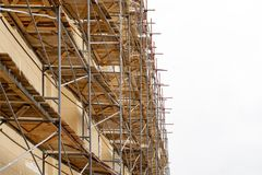Metal scaffolding with wooden decking built around a historic building for restoration work and renovation of the facade. Construc. Metal scaffolding with wooden Stock Image