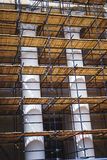 Metal scaffolding with wooden decking built around a historic building with columns for restoration work and renovation facade. Stock Photography