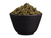 Metal Schüssel mit den chinesischen trockenen grünen Teeblättern, die auf Weiß lokalisiert werden lizenzfreies stockfoto