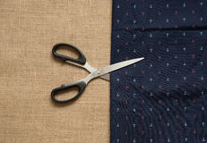 Metal scissors , and blue fabric with anchor ornament. Stock Photos