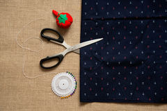 Metal scissors , and blue fabric with anchor ornament Stock Photos