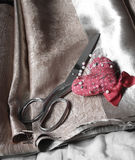 Metal scissors and pin on brown fabric royalty free stock photo