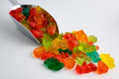 Colourful gummy candies. Metal scoop full of colorful gummy candies on white background stock photo