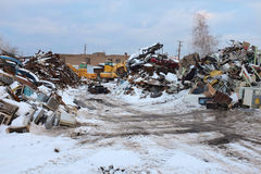 Metal Scrap Yard. Metal scrap piles are shown in recycling yard in winter with coating of snow accenting hard industrial setting royalty free stock images