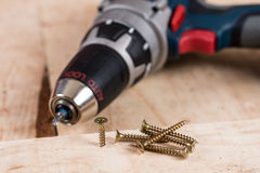 Metal screw screwed into a wooden board with accu drill Stock Photography