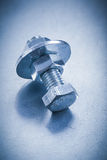 Metal screwbolt with bolt washer and screw nuts on. Metallic background construction concept Royalty Free Stock Images