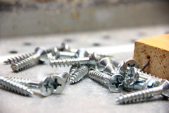 Metal Screws on Construction Site. Metal Screws on Natural Construction Site with wood and a nail in the backround Stock Images