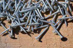 Metal screws on a wooden board close-up. Construction Materials.  Royalty Free Stock Photo