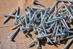 Metal screws on a wooden board close-up. Construction Materials.  Royalty Free Stock Images