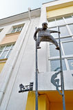 Metal sculpture of man on stilts made in modern style at the facade of Novgorod center of contemporary art in Veliky Novgorod, Rus Royalty Free Stock Photo