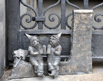 Metal sculptures of dwarfs, sitting and drinking beer. Stock Photography