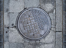 A metal sewer hatch is on the stone block pavement. Royalty Free Stock Images