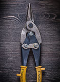 Metal sharp tin snips on wooden board construction Stock Photos