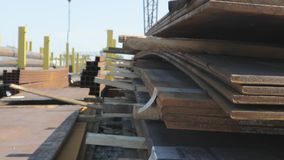Metal sheets on a metal skala under the open sky, good weather, metal sheets with a gantry crane in the background, a. Metal sheets on a metal skala under the stock footage
