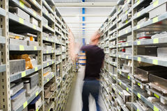 Metal shelves and technician at plant Stock Images