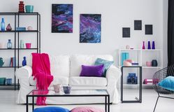 Metal shelves with vases behind white couch with pink blanket and purple and blue pillows, real photo. Concept royalty free stock photos