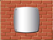 Metal shield on the brick wall Stock Photography