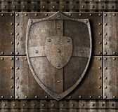 Metal shield over armour background. With rivets Royalty Free Stock Photo