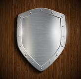 Metal shield on a wooden surface Royalty Free Stock Photography