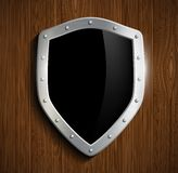Metal shield on a wooden surface Stock Photo