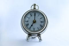 Metal and shiny clock stylized antique on a table on a light background. stock image