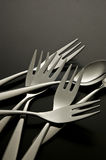 The metal shiny spoon and fork on black background. Close-up of a fork and spoon Royalty Free Stock Photos