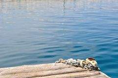 Metal ship chains and mooring bollard on wooden pier Royalty Free Stock Photography