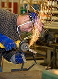 Metal Shop - Grinder. Student welder in metal shop, using a grinder to smooth his creation.  All work depicted is accurate and in accordance with industry safety Royalty Free Stock Photo