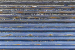 Metal shop shutter. Flaked paint metal shop shutter closed stock image