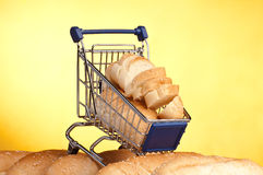 Metal shopping trolley filled with bread. On yellow stock images
