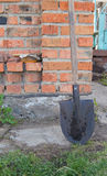 Metal shovel with wooden handle is a brick wall of the rural house Stock Photography