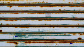 Metal shutter door. Gry color with rust running from humidity te Stock Image
