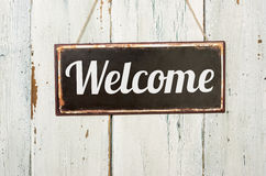 metal sign in front of a wooden wall - Welcome Stock Image