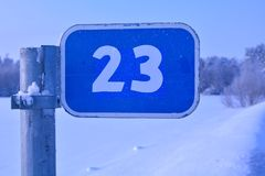 Road sign in winter field, twenty third kilometer stock photo