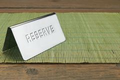 Metal Sign Reserve On The Restaurant Wood Table Background Stock Images