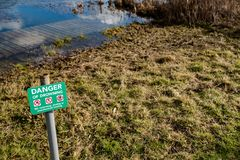 Danger of Drowning sign seen located near a deep river and quick sand area. stock photo