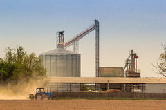 Metal silo tank in countryside field tractor on foreground Stock Photography