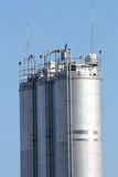Metal silos. Tall metal silos for storing grain against a blue sky Royalty Free Stock Photos
