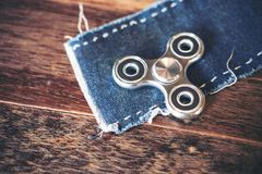 A metal silver color fidget spinner on jean cloth with wooden table background. Top view image of a metal silver color fidget spinner on jean cloth with wooden Royalty Free Stock Images