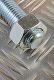 Metal silver fastener. A view of a nut and bolt laying on a chequered plate royalty free stock photo