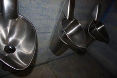 Metal silver urinals. Metal urinals. The men`s room Stock Image