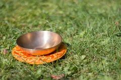 Singing bowl in the own garden, zen outdoors. Metal singing bowls in the grass of the own garden, zen wellness massage buddhism yoga alternative medicine nature royalty free stock photos