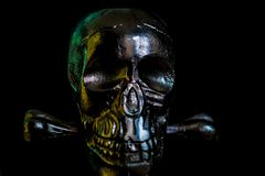 Metal skull on black background. Ominous glare on a metallic skull in the dark royalty free stock photo