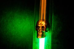 Metal Skull Placed in Flask and Illuminated by Green Light on Dark Background. Super noisy and sharp. Alchemical, magical and experimental atmosphere Stock Images