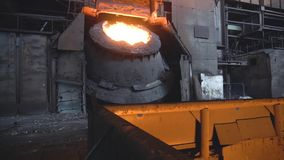 Metal smelting in steel mill furnace. Footage. Top view on pot of solidified metal next to sprinkles and sparks of hot. Metal. Heavy industry and metal smelting stock photo