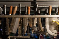 Metal smith sharpening farm tools and knives stock image
